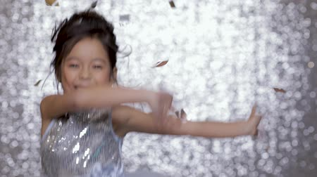 幼稚な : cute happy little girl child in a silver dress dancing on background of silver bokeh. 動画素材