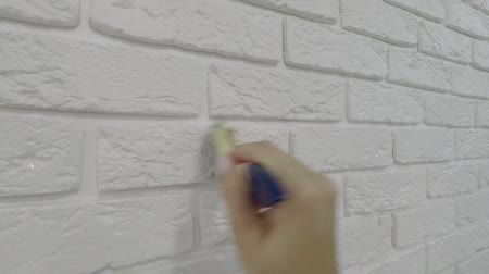 zedník : worker manually varnishes decorative brick on the wall.