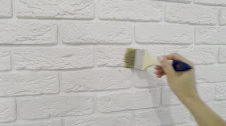 кирпичная кладка : worker manually varnishes decorative brick on the wall.