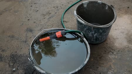 desenhada à mão : full bucket of water and a hose at the construction site. water is drawn to mix concrete solution Stock Footage