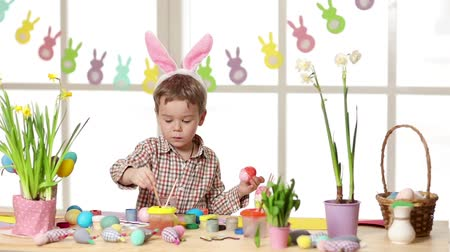 narciso : Happy child wearing bunny ears painting eggs on Easter day. Little boy preparing for the Easter.