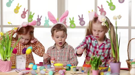 easter : Happy children wearing bunny ears painting eggs on Easter day. Little girls preparing for the Easter.