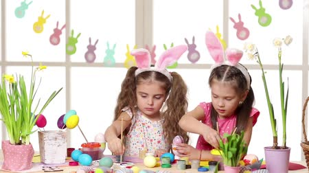 narciso : Happy children wearing bunny ears painting eggs on Easter day. two little girls preparing for the Easter. Stock Footage