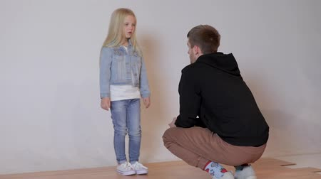 back side : professional photographer talking to a cute little model girl at a photo shoot in a photo studio. the photographer explains to the child how to pose