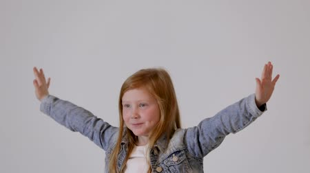 miscellaneous : happy smiling little red-haired girl posing in photo studio. Childrens photo session on a white background.