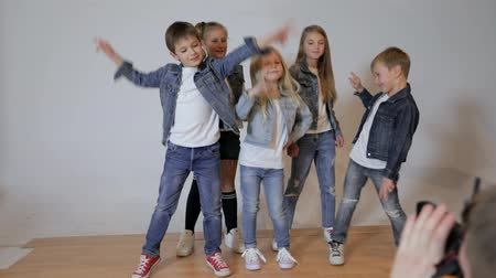 denim : Photographer taking pictures of happy children posing in photo studio. Childrens photo session Stock Footage