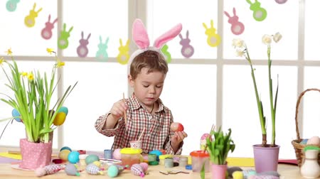 rabbits : Happy child wearing bunny ears painting eggs on Easter day. Little boy preparing for the Easter.