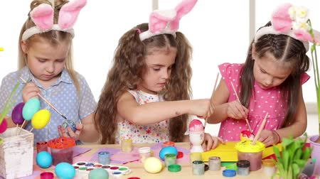 rodzeństwo : Happy children wearing bunny ears painting eggs on Easter day. Little girls preparing for the Easter.