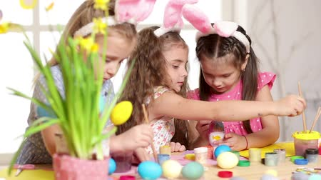 narciso : Happy children wearing bunny ears painting eggs on Easter day. Little girls preparing for the Easter.