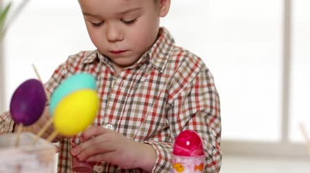 кролик : Happy child wearing bunny ears painting eggs on Easter day. Little boy preparing for the Easter.