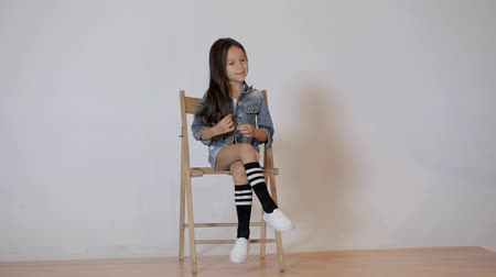 lő : Cute little girl posing in photo studio. Childrens photo session on a white background. kid sitting on a chair Stock mozgókép