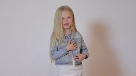 gram : Cute blonde little girl posing in photo studio. Childrens photo session on a white background. Close-up