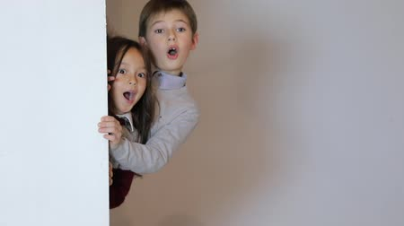 엿보기 : surprised children looking out from behind white blank placard. Kid girl and boy posing in a studio. Copy space.