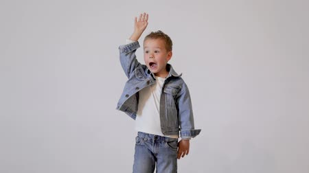 gram : Cute little boy posing in photo studio. Childrens photo session on a white background.