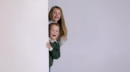 signe non fumeur : smilig children looking out from behind white blank placard. Kid girl and boy posing in a studio. Copy space.