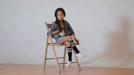 models : Cute little girl posing in photo studio. Childrens photo session on a white background. kid sitting on a chair Stock Footage