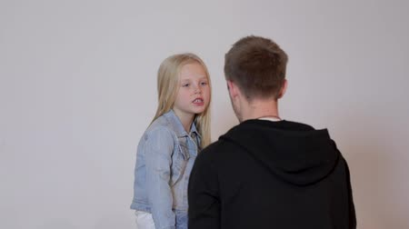 magyarázza : professional photographer talking to a cute little model girl at a photo shoot in a photo studio. the photographer explains to the child how to pose