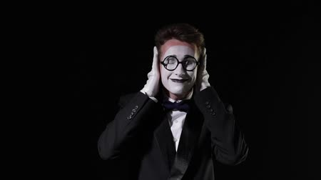 ator : mime shows gesture see nothing hear nothing say nothing on black background