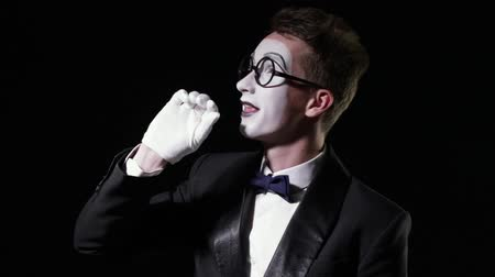 отношение : Young mime man in texudo waving his hand and falls down on black background. slow motion