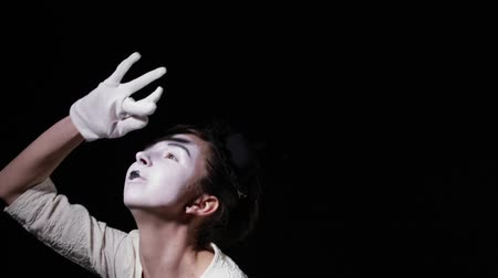 shattering : Close-up of mime woman shows different emotions on black background