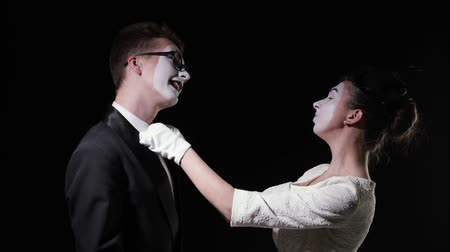 mluvení : love couple mimes. girl mime in dress removes dust particles from a man mime and hugs him