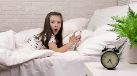 mentiras : cute little child girl lies in bed uses digital tablet. surprised child playing on tablet pc and looking at camera. slow motion