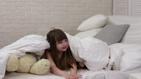 ищу : two cute little children girls cover with blanket. Playing hide and seek, peek boo. slow motion