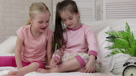pajama : kids drawing pictures while lying on bed. pajama party and friendship. Stock Footage