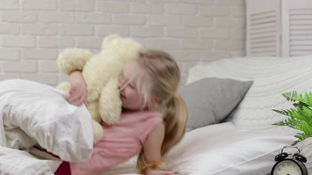 плюшевый мишка : cute little child girl wakes up from sleep and hug teddy bear in bed in the morning