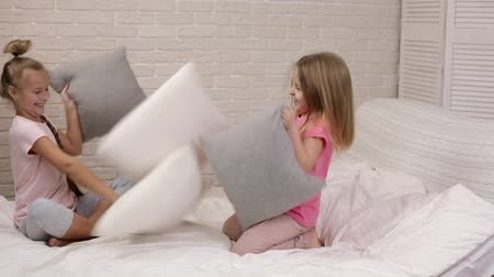 ベッドルーム : two cute children girls playing with pillow in the bedroom. pajama party and friendship. 動画素材