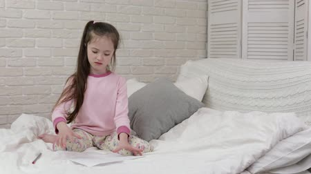 nem sikerül : little girl drawing pictures while lying on bed.drawing fails. upset child crumples the sheet and throws it away