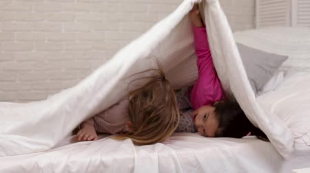 скрывать : two cute little children girls cover with blanket. Playing hide and seek, peek boo Стоковые видеозаписи