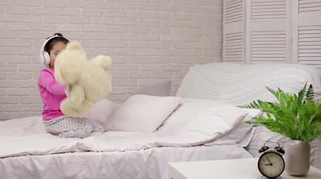 life energy : little child baby girl listening to the music with the headphones and dancing with teddy bear on bed. happy morning Stock Footage
