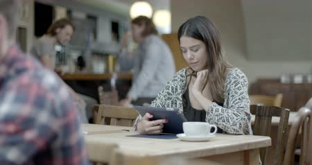 чувствительный : Woman thinking and using digital tablet while sitting in pub