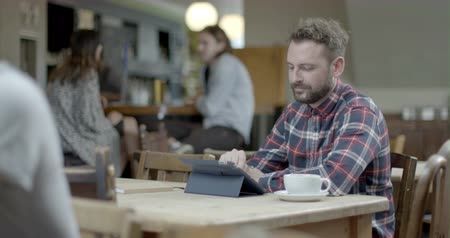 чувствительный : Man using digital tablet and drinking coffee while sitting in pub