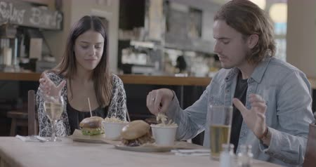 diferansiyel odak : Man and woman enjoying drink and eating french fries in pub Stok Video