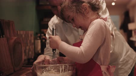 legyintés : Father and daughters making pancake in kitchen, daughter mixing dough in bowl