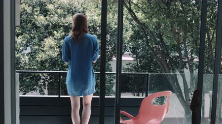 legs only : Young woman holding cup of black tea and sitting on chair in balcony Stock Footage
