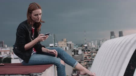 legs only : Young woman sitting on terrace and text messaging  city in background Stock Footage