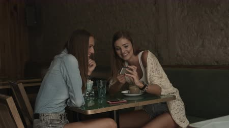 calças : Female friends holding mobile phone and discussing while sitting in coffee bar