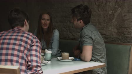 checked pattern : Friends laughing and talking while sitting in coffee bar Stock Footage