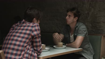 checked pattern : Male friends sitting and talking in coffee bar