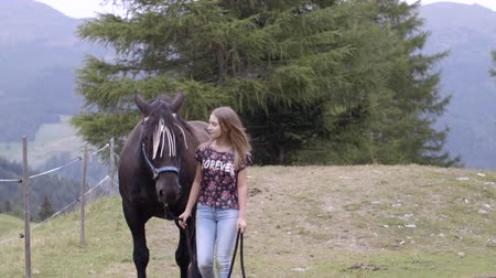 trusting : Girl walking with horse in countryside Stock Footage