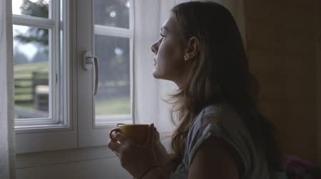 faház : Woman looking out of window with mug
