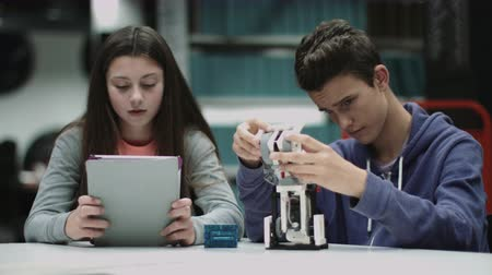 manichino : Teenage boy and girl working with digital tablet and robot in library