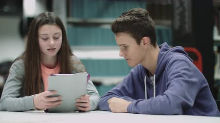menores : Teenage boy and girl working on digital tablet in library Archivo de Video