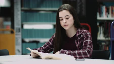school children : Girl in a school library reading a book Stock Footage