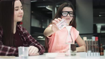 tests : Girls practice chemistry at school Stock Footage