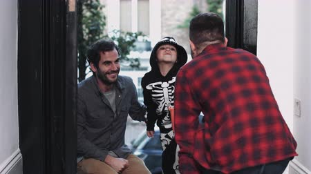 pai : Child in Halloween costume receiving candy at door