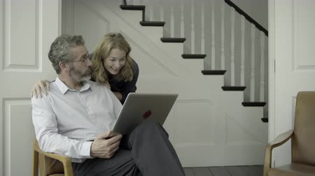 affluent : Senior Adult couple working from home on laptop